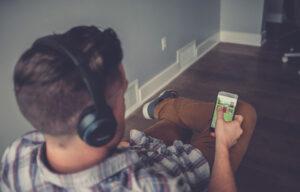 Parente spia di nascosto attraverso uno smartphone e un paio di cuffie